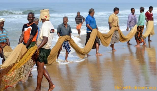 Пляж с черным песком и рыбаки