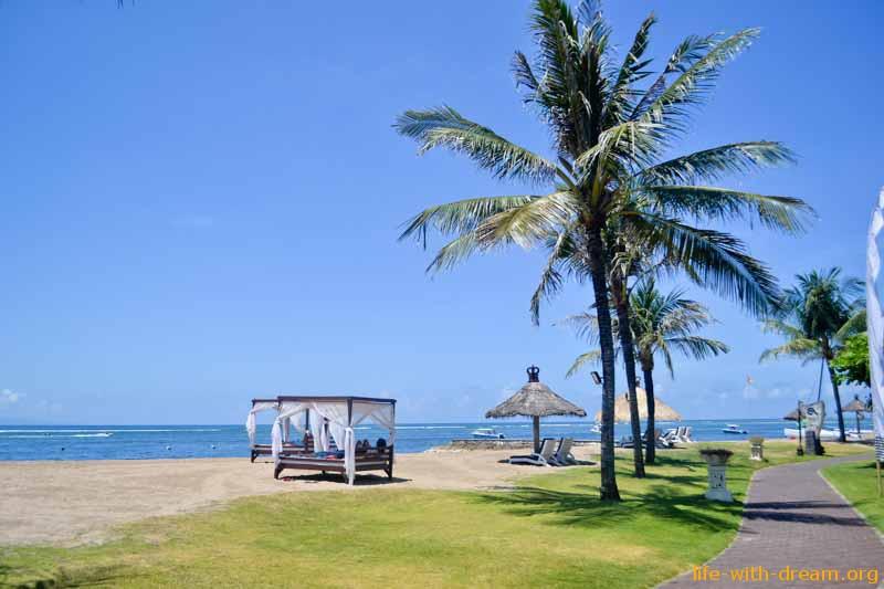Уютные лежаки в виде кроватей на пляже в Grand Mirage Resort Thallaso Bali